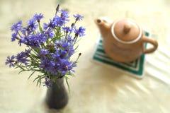 Ramo de cornflowers azules en florero y una caldera Imagen de archivo