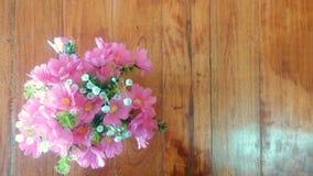 Ramo de Daisys rosado en la tabla de madera imagenes de archivo