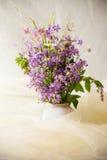 Ramo de flor del prado en el florero blanco con la tela transparente ligera Foto de archivo libre de regalías