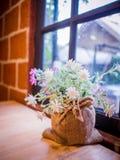 Ramo de flor falsa en bolso del saco imagen de archivo libre de regalías