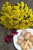 Ramo de flores amarillas, de hoja roja y de placa con las galletas, en a Fotos de archivo