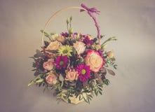 Ramo de flores brillantes en cesta en colores del vintage Fotografía de archivo