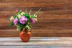 Ramo de flores del trébol, de acianos y del jazmín en un jarro de la loza de barro en una tabla de madera en un fondo retro marró Foto de archivo