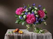 Ramo de flores en un florero y melocotones Fotos de archivo