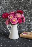 Ramo de flores en un jarro blanco y un regalo hecho a mano en papel del arte fotografía de archivo libre de regalías
