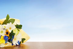 Ramo de flores en una superficie de madera contra el cielo azul Imagenes de archivo
