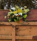 Ramo de flores que se pegan hacia fuera de un envase de basura Foto de archivo libre de regalías