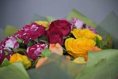 Ramo de flores rojas y amarillas hermosas en verde Foto de archivo