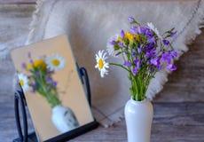 Ramo de flores salvajes en una tabla de madera con una reflexión en el espejo Fotografía de archivo