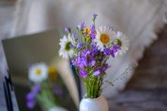 Ramo de flores salvajes en una tabla de madera con una reflexión en el espejo Fotos de archivo