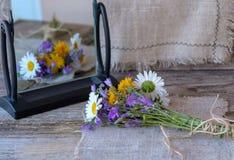 Ramo de flores salvajes en una tabla de madera con una reflexión en el espejo Imagenes de archivo