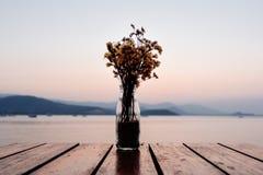 Ramo de flores secadas en el tarro de cristal con las flores secadas en la madera imagen de archivo libre de regalías