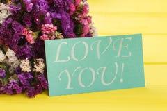 Ramo de flores y de tarjeta del statice con te amo lema fotos de archivo libres de regalías