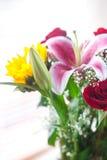 Ramo de girasoles, de lirio y de rosas en un florero Imagen de archivo libre de regalías