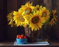 Ramo de girasoles en una cesta y tomates Imagenes de archivo