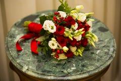 Ramo de la boda con las bayas rojas y rosas blancas y rojas y cintas Imagen de archivo libre de regalías