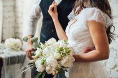 Ramo de la boda con las peonías en manos de la novia Foto de archivo libre de regalías
