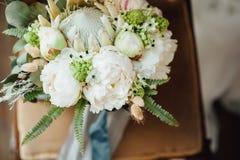 Ramo de la boda con las peonías que se colocan en una ventana Foto de archivo libre de regalías