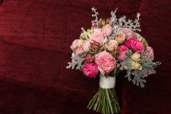 Ramo de la boda con las rosas púrpuras y rosadas Los accesorios de la boda están mintiendo en una butaca roja Foto de archivo