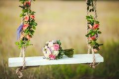 Ramo de la boda de peonías que mienten en el oscilación blanco del banco adornado con las flores frescas Foto de archivo libre de regalías
