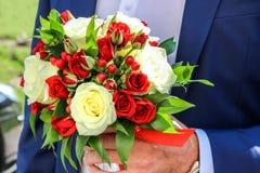 Ramo de la boda de rosas rojas y blancas y de hypericum en la mano del novio Foto de archivo