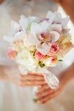 Ramo de la boda en las manos de la novia con las rosas del anf de las orquídeas Imagen de archivo libre de regalías