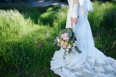 Ramo de la boda en las manos de la novia contra la perspectiva del verdor Fotografía de archivo libre de regalías