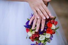 Ramo de la boda - manos del ` s del novio y de la novia Fotos de archivo