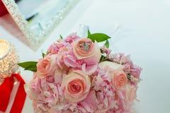 Ramo de la boda de rosas y de anillos de bodas rosados en una tabla de madera Copie el espacio El concepto de una boda, de un par Fotografía de archivo libre de regalías