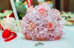 Ramo de la boda de rosas y de anillos de bodas rosados en una tabla de madera Copie el espacio El concepto de una boda, de un par Imagen de archivo