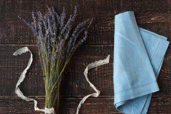 Ramo de la lavanda y una servilleta azul en el fondo de madera oscuro Imagenes de archivo