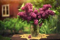 Ramo de la lila en tejido hecho punto en el cierre cristalino del florero encima de la foto del vintage Imagen de archivo libre de regalías