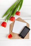 Ramo de la primavera de tulipanes rojos y de teléfono móvil negro Foto de archivo