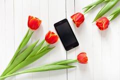 Ramo de la primavera de tulipanes rojos y de teléfono móvil negro Fotos de archivo
