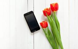 Ramo de la primavera de tulipanes rojos y de teléfono móvil negro Imágenes de archivo libres de regalías