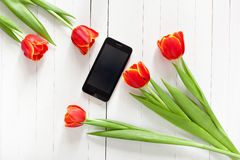 Ramo de la primavera de tulipanes rojos y de teléfono móvil negro Imagen de archivo libre de regalías