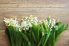 Ramo de la primavera de los lirios del valle, lirio de los valles en un fondo de madera fotos de archivo