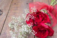 Ramo de la tarjeta del día de San Valentín de tres rosas rojas con el flowe blanco del gypsophila Fotos de archivo libres de regalías