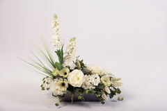 Ramo de las flores artificiales en el florero en blanco Fotos de archivo