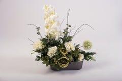 Ramo de las flores artificiales en el florero en blanco Fotografía de archivo