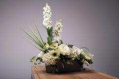 Ramo de las flores artificiales en florero en la tabla Fotografía de archivo libre de regalías