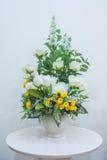 Ramo de las flores artificiales en florero en la tabla Fotos de archivo libres de regalías