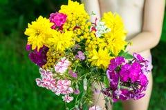Ramo de las flores salvajes en manos del niño Imágenes de archivo libres de regalías