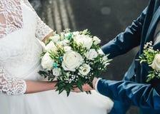 Ramo de las rosas blancas en las manos de la novia y del novio Imagen para casarse blogs, saludando tarjetas de la invitación Imagen de archivo