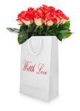 Ramo de las rosas rojas en el bolso blanco aislado Foto de archivo libre de regalías
