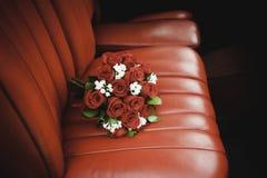 Ramo de las rosas rojas sobre el coche de cuero rojo Foto de archivo