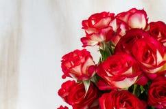 Ramo de las rosas rojas sobre la tabla de madera blanca Imagen de archivo