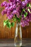 Ramo de lila en un florero en los tableros Fotografía de archivo libre de regalías