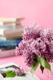 Ramo de lila y de libros en fondo rosado Imagenes de archivo