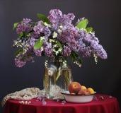 Ramo de lila y de lirios del valle en un tarro y una FRU de cristal Imágenes de archivo libres de regalías